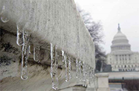 Photo of the U.S. Capital in the background and a corner of a nearby building with icicles.